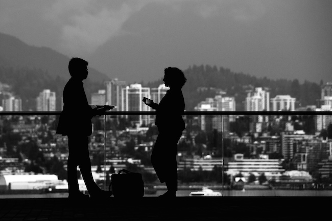 image of two people talking on a hotel balcony overlooking a scenic cityscape